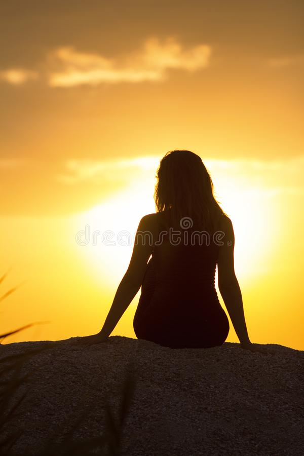 Schattenbild des schönen durchdachten Mädchens, das auf dem Sand sitzt und den Sonnenuntergang, die Zahl der jungen Frau auf dem  lizenzfreie stockfotografie