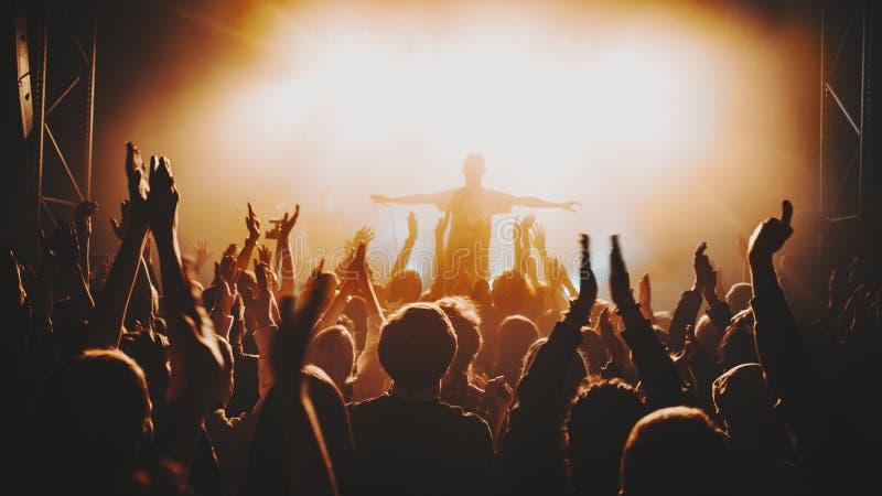 Schattenbild des Solisten/des Sängers steht in einem Nebel in den Strahlen des Lichtes Konzertpublikum vor hellen Stadiumslichter stockbilder