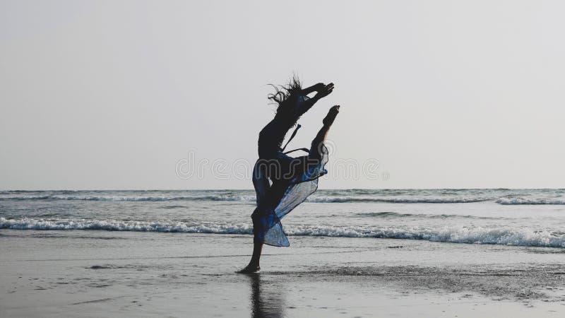 Schattenbild des Tanzens der jungen Frau mit gymnastischen Elementen am sandigen Strand stockfotografie