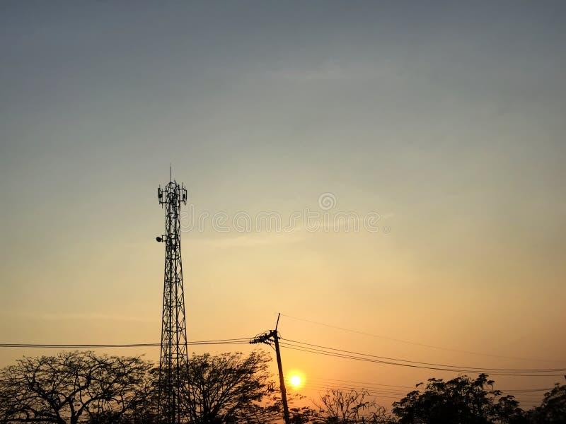 Schattenbild des Telekommunikationsturms, der Linien der elektrischen Leistung und der Baumaste während des Sonnenuntergangs lizenzfreie stockbilder