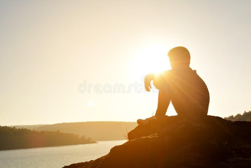 Schattenbild des traurigen Jungen und des Sitzens auf dem Felsen im Fluss stockfotografie