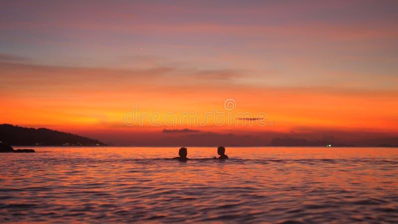 Schattenbild des Vaters und des kleinen Sohns, die im Meer bei schönem Sonnenuntergang baden Reisefeiertagskonzept lizenzfreie stockfotos