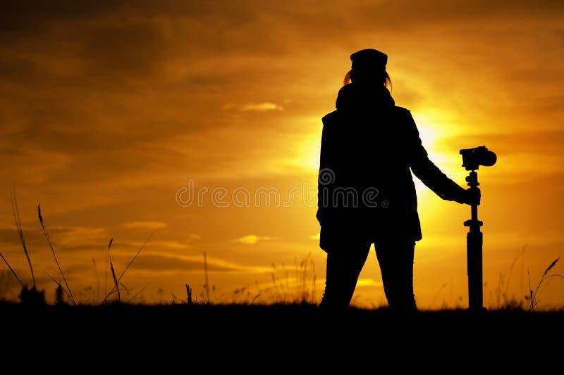 Schattenbild des weiblichen Fotografen gegen Sonnenuntergang stockfotografie