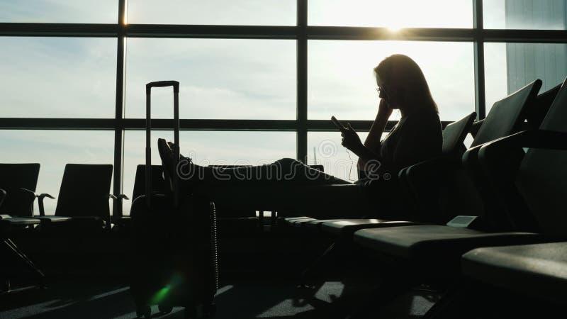Schattenbild einer erfolgreichen Frau im Flughafenabfertigungsgebäude Das Warten auf den Flug benutzt einen Smartphone und Kopfhö stockbild