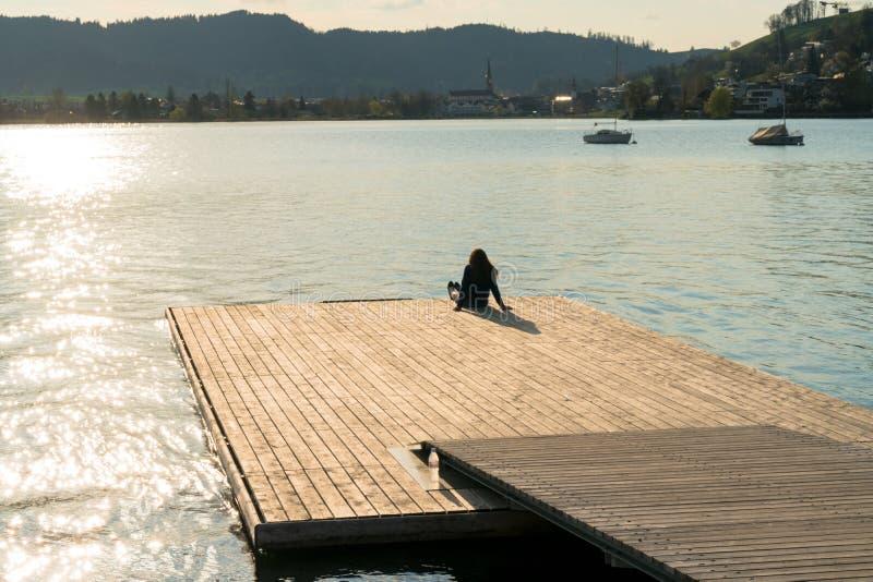 Schattenbild einer Frau, die auf einem Schwimmdock auf einem See bei Sonnenuntergang sich entspannt lizenzfreies stockbild