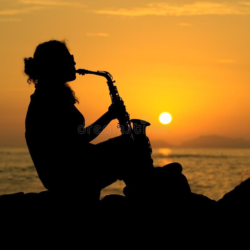 Schattenbild einer Frau, die das Saxophon spielt stockfotos