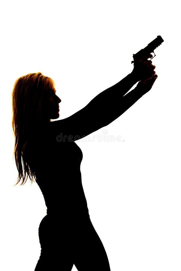 Schattenbild einer Frau, die ein Gewehr auf den Seitenabschluß zeigt lizenzfreies stockbild