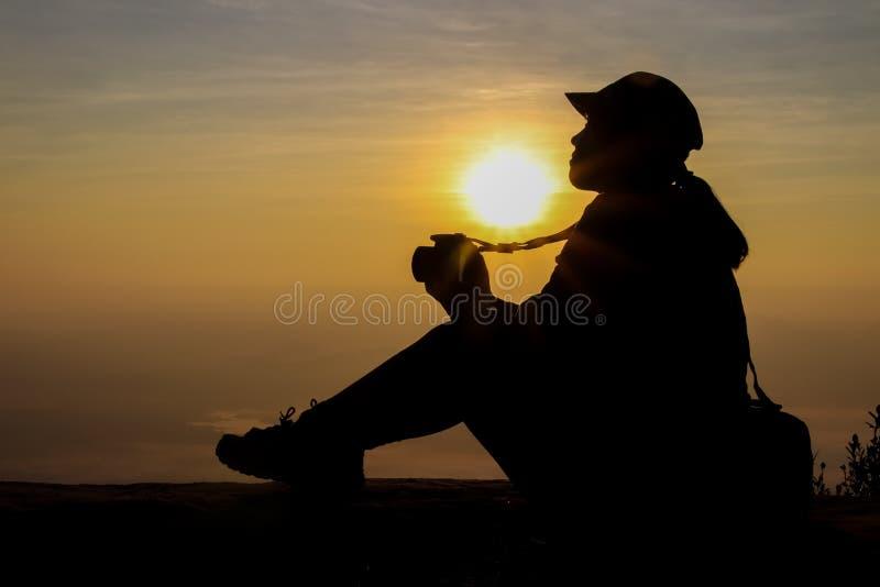 Schattenbild einer Frau, die eine Kamera macht Fotos draußen während des Sonnenaufgangs oder des Sonnenuntergangs hält stockbild