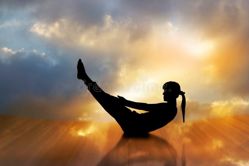 Schattenbild einer Frau, die Yoga auf Bretterboden mit dem vibrierenden Hintergrund ausübt stockfotos