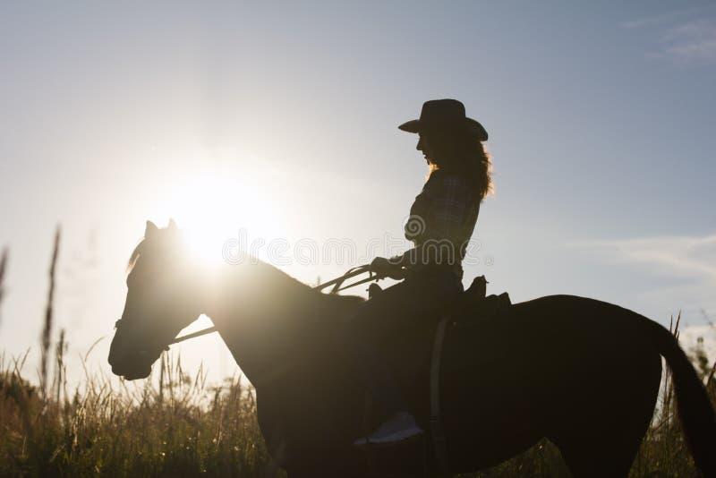 Schattenbild einer Frau im Cowboyhut, der ein Pferd - Sonnenuntergang oder Sonnenaufgang, horizontal reitet lizenzfreie stockfotografie