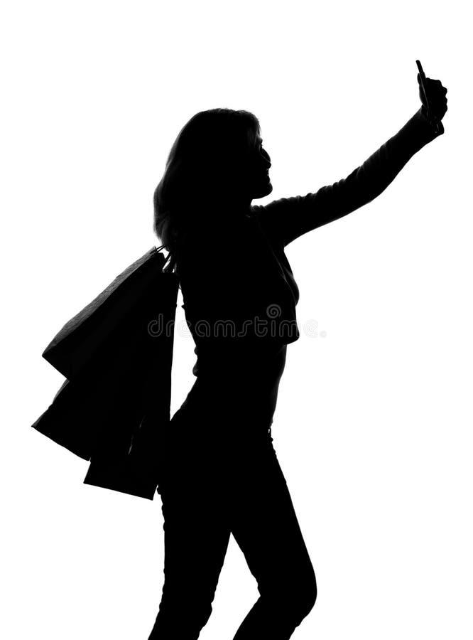 Schattenbild einer Frau mit den Einkaufstaschen, die selfie tun lizenzfreie stockfotografie