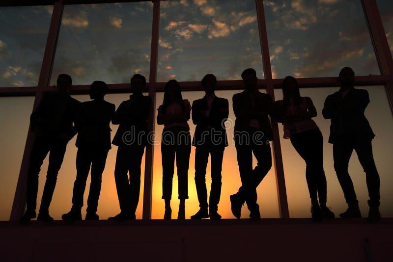 Schattenbild einer Gruppe Geschäftsleute, die nahe dem Bürofenster stehen lizenzfreie stockbilder