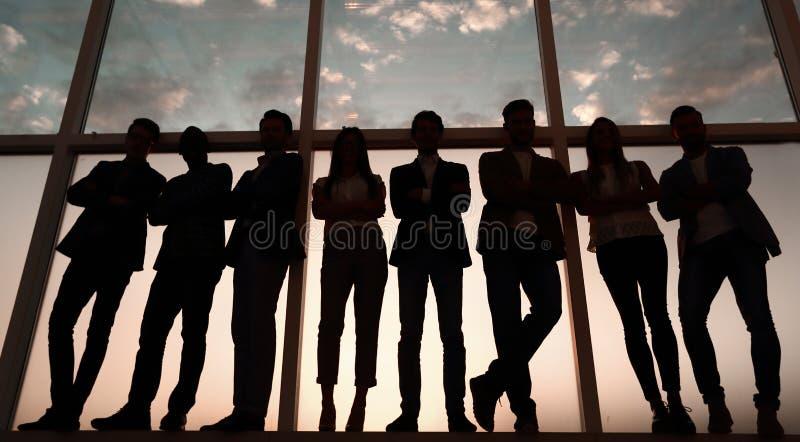 Schattenbild einer Gruppe Geschäftsleute, die nahe dem Bürofenster stehen stockfotos