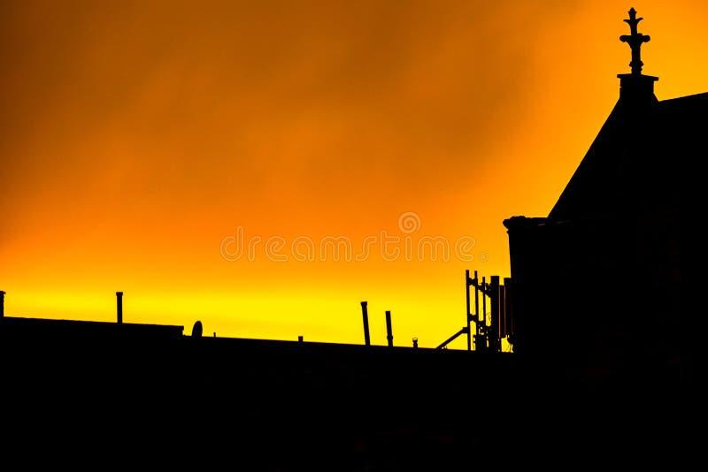 Schattenbild einer Harlem-Dachspitze, der Kamine und des Kirchenkirchturms, gegen einen hellen gelben, brennend-aussehenden Himme stockfotos