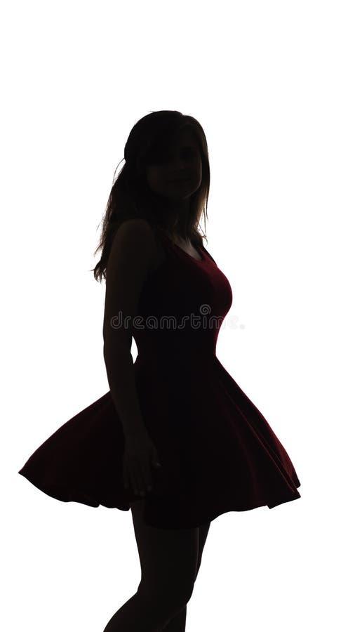 Schattenbild einer jungen eleganten unbekannten Frau in einem Kleid und, Zahl des schönen Mädchenkörpers auf einem weißen lokalis lizenzfreie stockfotografie