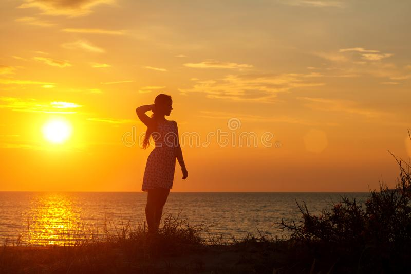 Schattenbild einer jungen Frau auf dem Strand bei Sonnenuntergang lizenzfreies stockfoto