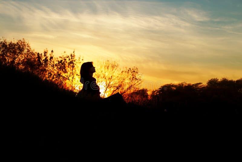 Schattenbild einer jungen Frau, die auf einem Hügel bei Sonnenuntergang, ein Mädchen geht in den Herbst auf dem Gebiet sitzt lizenzfreie stockfotos