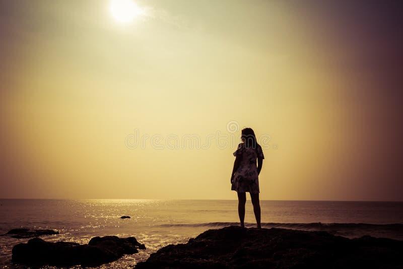 Schattenbild einer jungen Frau vor dem hintergrund des Meeres und der Sonne lizenzfreies stockbild