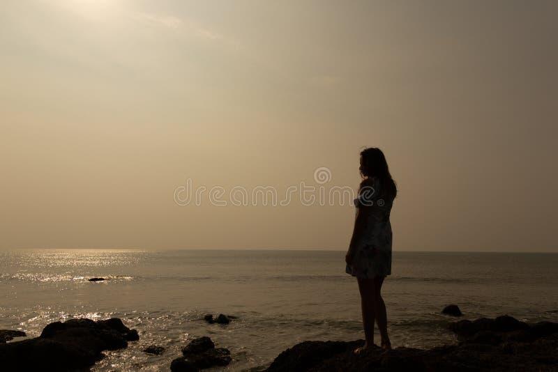Schattenbild einer jungen Frau vor dem hintergrund des Meeres und der Sonne stockbilder