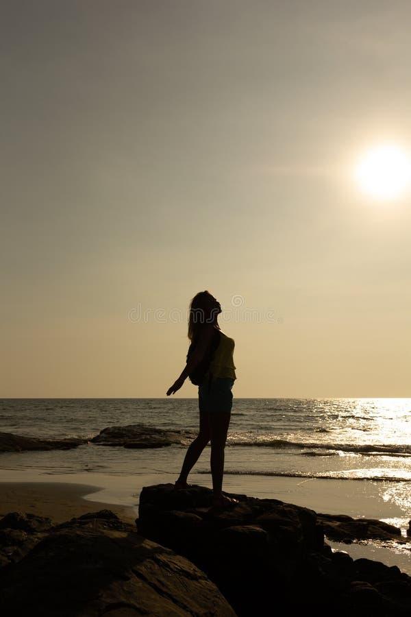 Schattenbild einer jungen Frau vor dem hintergrund des Meeres und der Sonne lizenzfreie stockfotografie