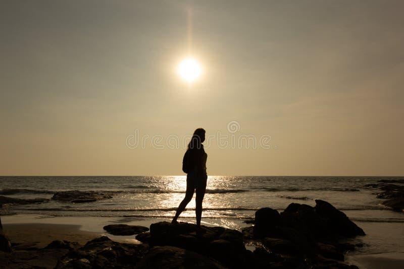 Schattenbild einer jungen Frau vor dem hintergrund des Meeres und der Sonne stockfotografie