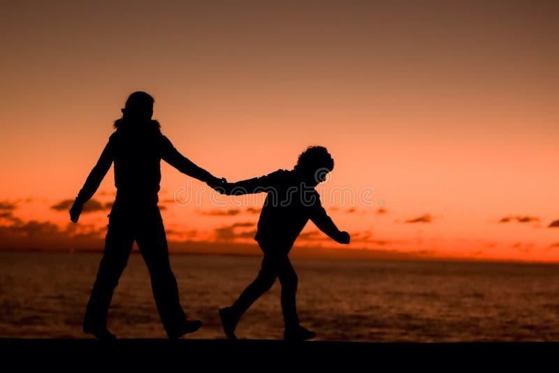 Schattenbild einer jungen Mutter und ihres Sohngehens lizenzfreie stockfotografie