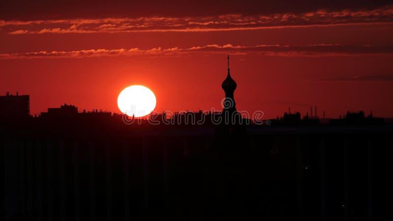 Schattenbild einer Kirchenspitzenhaube bei einem tiefroten Sonnenuntergang lizenzfreie stockbilder
