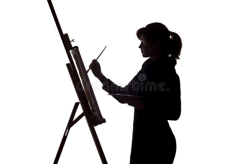 Schattenbild einer Malerei der jungen Frau auf einem Gestell auf einem weißen lokalisierten Hintergrund, der Mädchenfigur mit ein lizenzfreie stockfotografie