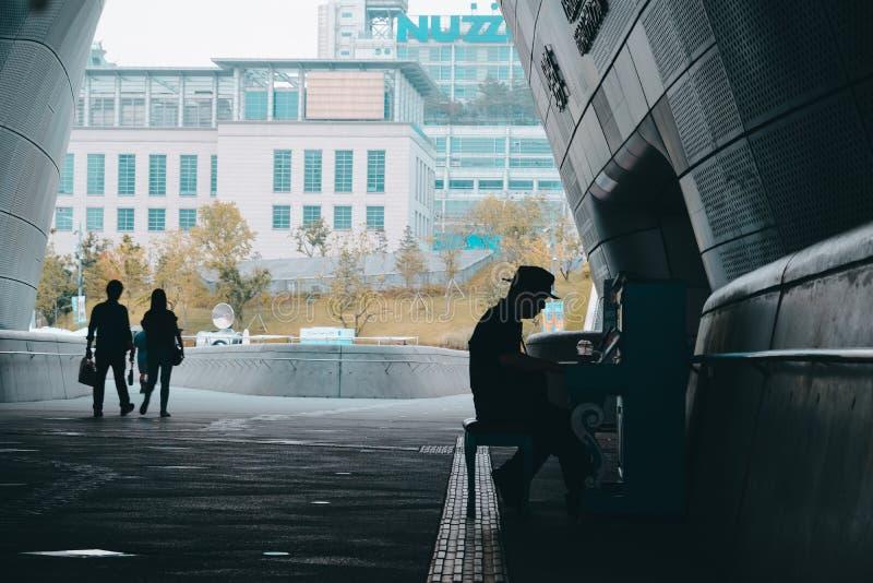 Schattenbild einer Person in einem Hut, der das Klavierfreien und -leute gehen vorbei in den Hintergrund spielt lizenzfreies stockbild