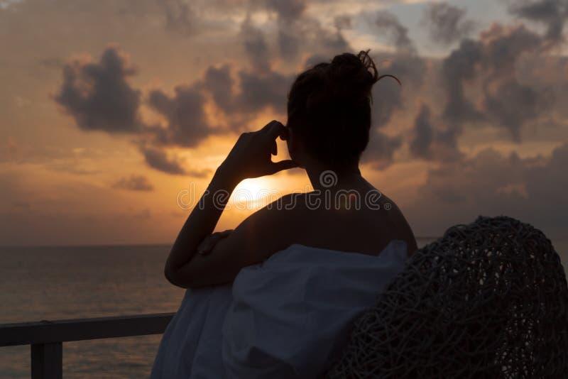 Schattenbild einer Sch?nheit, die Sonnenaufgang von einem Balkon ?ber dem Meer erw?gt stockbild