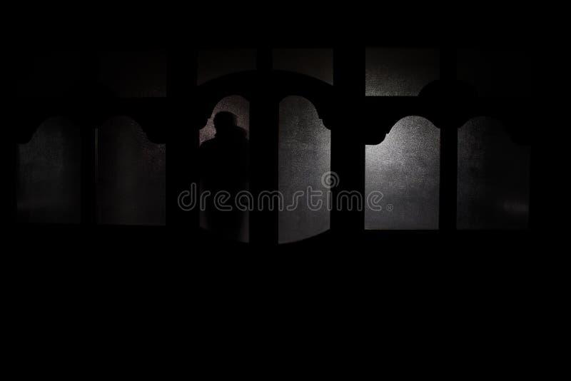 Schattenbild einer unbekannten Schattenzahl auf einer Tür durch eine geschlossene Glastür Das Schattenbild eines Menschen vor ein stockfotos