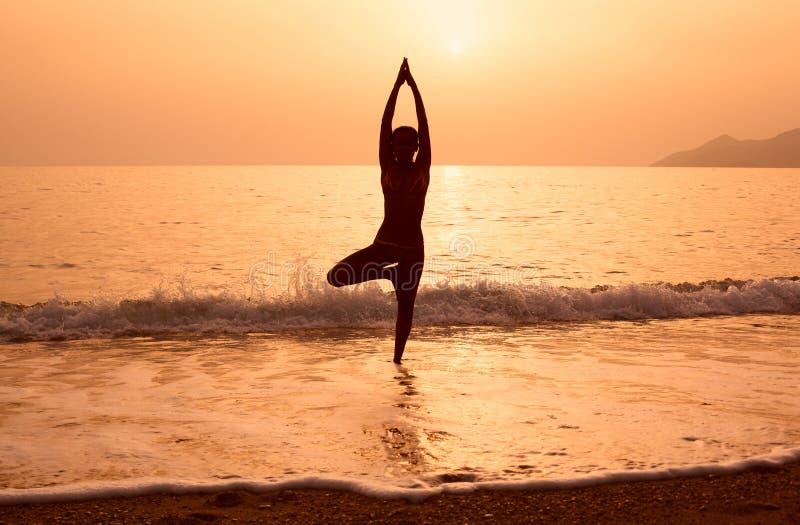 Schattenbild eines übenden Yoga des Mädchens auf dem Seestrand stockfotos