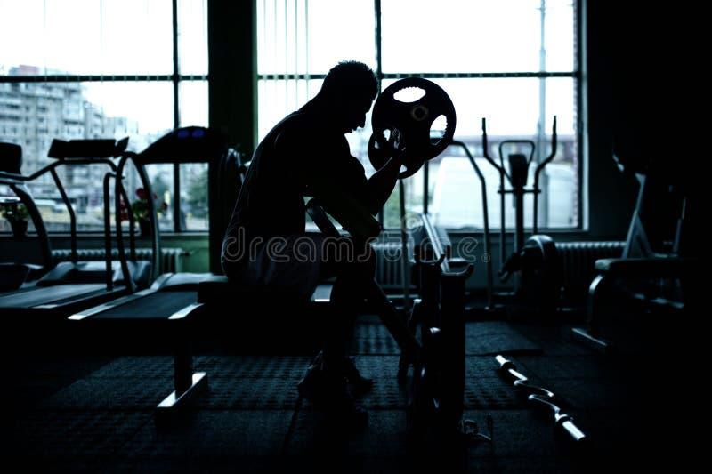 Schattenbild eines athletischen Mannes, der an der Turnhalle ausarbeitet stockfotografie