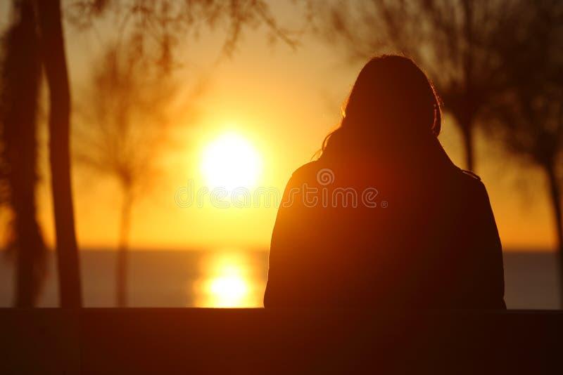 Schattenbild eines aufpassenden Sonnenuntergangs der einsamen Frau im Winter stockfoto