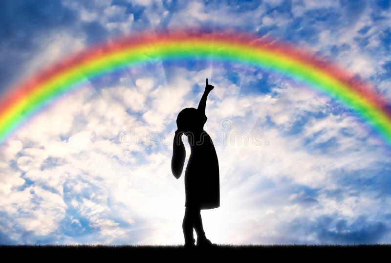 Schattenbild eines Babys, das einen Finger im Himmel auf einem Regenbogen zeigt kindheit lizenzfreie stockbilder