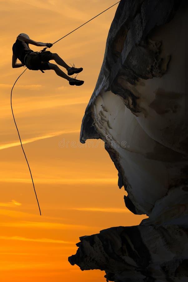 Schattenbild eines Bergsteigers über schönem Sonnenuntergang lizenzfreies stockfoto