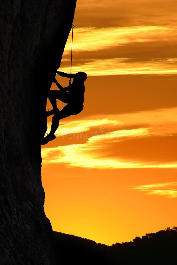 Schattenbild eines Bergsteigers über schönem Sonnenuntergang lizenzfreie stockfotografie