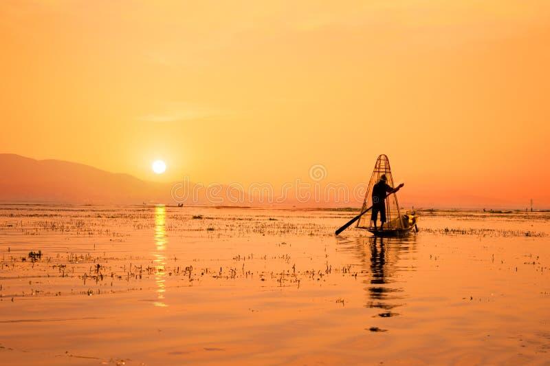 Schattenbild eines birmanischen Fischers auf Bambusboot bei Sonnenuntergang Inle See, Myanmar Birma, Reiseziel lizenzfreie stockfotos