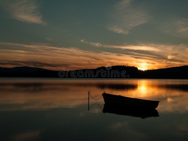 Schattenbild eines Bootes auf einem See mit Sonnenuntergang lizenzfreies stockbild