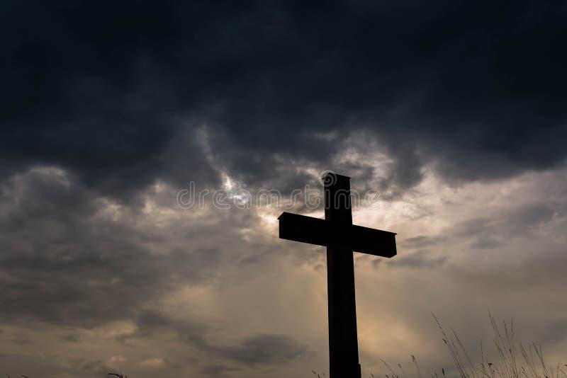 Schattenbild eines einfachen katholischen Kreuzes, drastische stormclouds stockfotografie