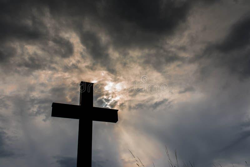 Schattenbild eines einfachen katholischen Kreuzes, drastische stormclouds nach starkem Regen lizenzfreie stockfotos