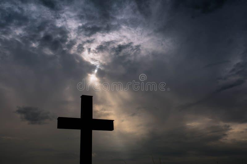 Schattenbild eines einfachen katholischen Kreuzes, drastische stormclouds stockfoto