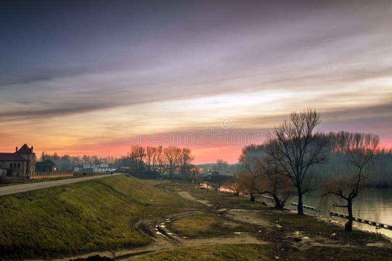 Schattenbild eines einsamen Mannes im Abstand im Sonnenuntergang in der Flussbank lizenzfreie stockfotos