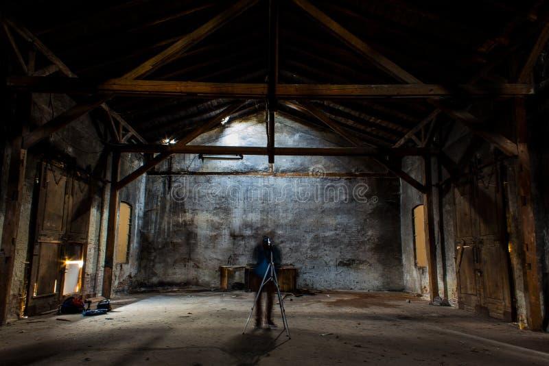 Schattenbild eines Fotografen mit einem Stativ in einem großen leeren Raum lizenzfreies stockbild