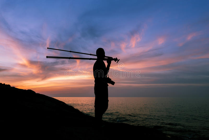 Schattenbild eines Fotografen oder des Reisenden mit dem Stativ, der an steht lizenzfreies stockbild