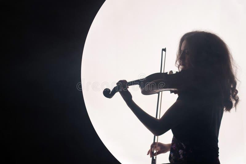 Schattenbild eines Frauenviolinisten in einem weißen Halbrund mit Rauche auf einem schwarzen Hintergrund Ein Konzept für Musik wä lizenzfreie stockfotografie
