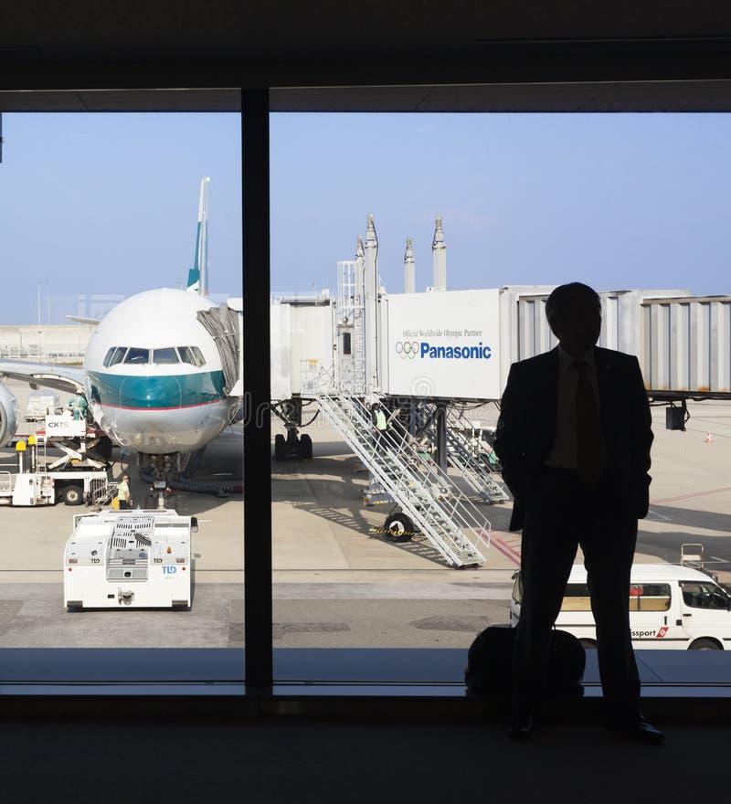 Schattenbild eines Geschäftsmannwartec$verschalens in einem Flughafen lizenzfreie stockfotos