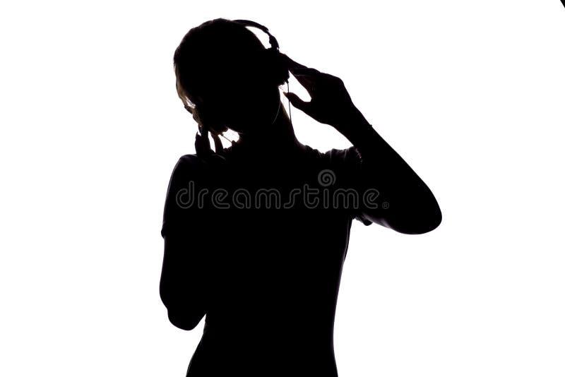 Schattenbild eines hörenden Liedes und der Entspannung des glücklichen Mädchens in den Kopfhörern, Zahl von tennager bewegend auf stockfotografie