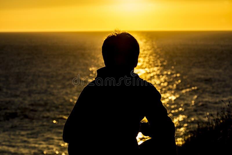 Schattenbild eines Jugendlichjungen auf Sonnenuntergang lizenzfreies stockfoto
