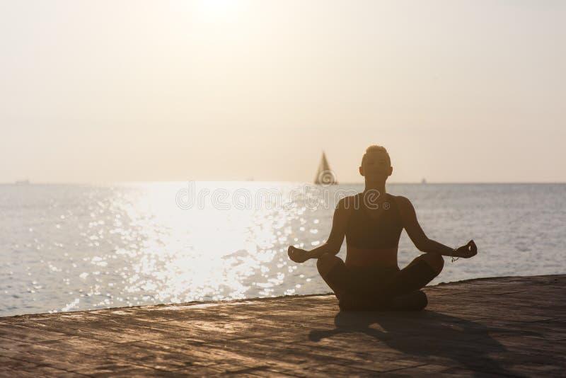 Schattenbild eines jungen athletischen Mädchens, das an Yoga bei Sonnenaufgang auf dem Strand mit einem Segelboot teilnimmt lizenzfreies stockfoto